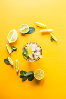 Ice tea with ice, lemon and mint on a combined colored yellow background.