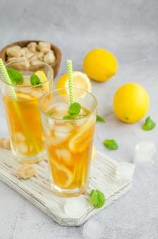 Холодный чай с лимоном, коричневым сахаром, листьями мяты и кубиками льда в стакане на доске на светлом фоне. летний освежающий напиток.