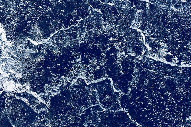 Текстура льда с замороженными пузырями и трещинами на синем фоне. красивый абстрактный декоративный фон. стильный абстрактный дизайн для упаковки, подарка, ткани, текстиля, мебели. зимний узор.