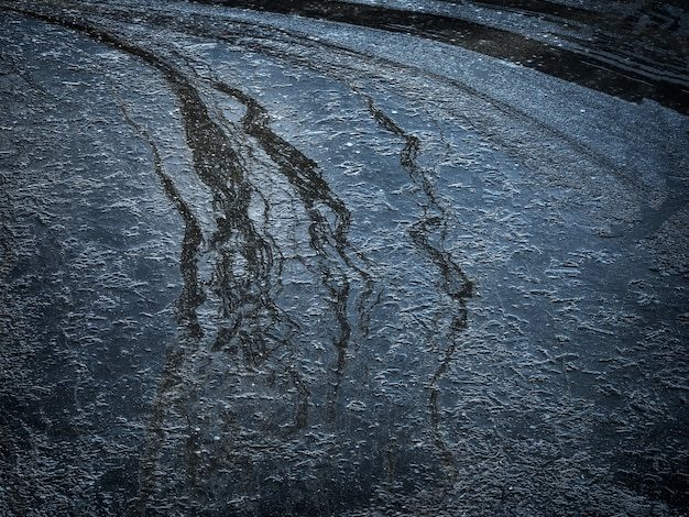 Ice with abstract streaks on the surface. natural dark background with ice on the river