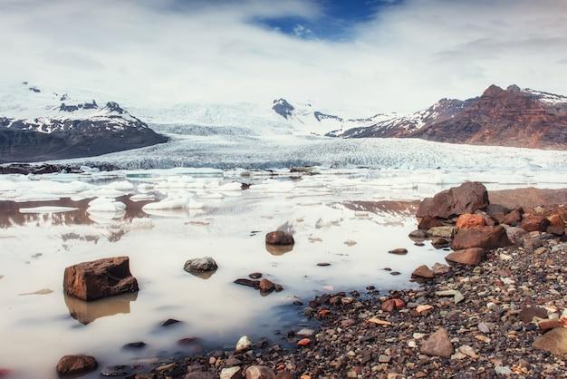 Айсберг ледник лагуна фьялсарлон. кучевые белые облака отражают