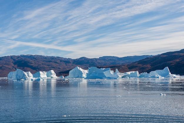 穏やかな水の反射とグリーンランドフィヨルドの氷山。日当たりの良い天気。ゴールデンアワー。