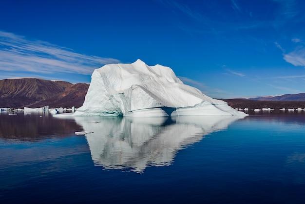 Айсберг в фьорде гренландии с отражением в спокойной воде. солнечная погода. золотой час