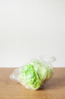 Iceberg lettuce vegetable in plastic bag. single use plastic packaging issue