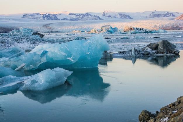 アイスランドの雪に覆われたヨークルサルロンの凍った水の近くの氷山