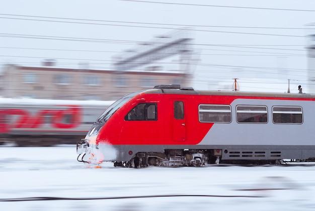 Покрытый льдом дизельный поезд мчится по размытому зимнему железнодорожному ландшафту