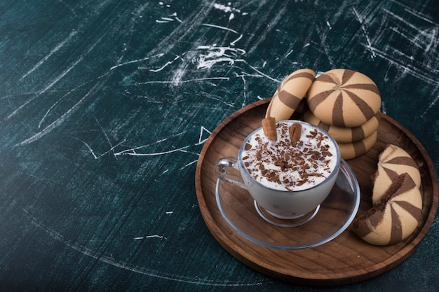 Icecream with cocoa cookies in a wooden platter, angle view