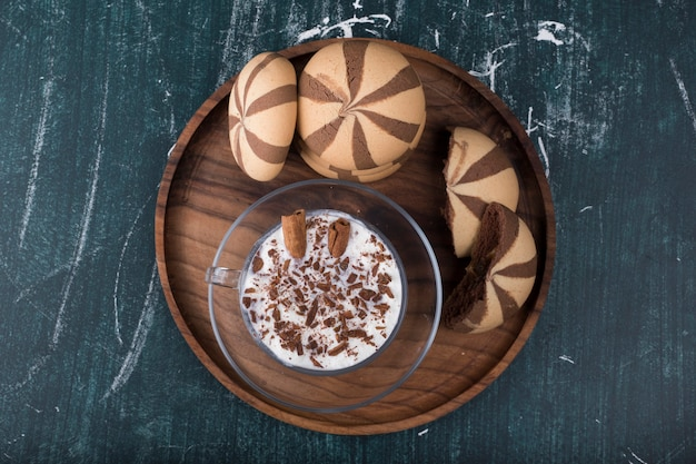 Icecream with cocoa cookies in a wooden platter, top view