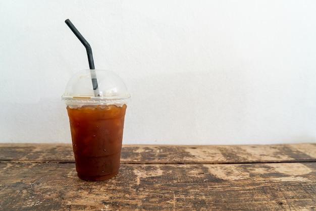 Черный кофейный стакан со льдом американо на деревянный стол