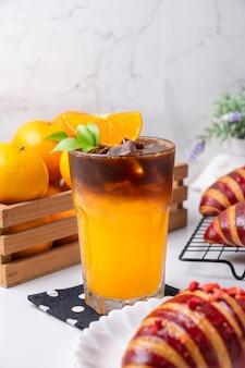 크로와상과 오렌지로 장식된 신선한 오렌지 주스 층에 아이스 아메리카노 블랙 커피