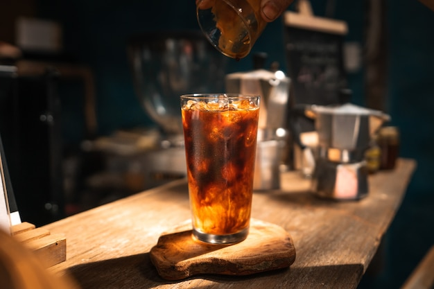 Iced americano coffee in a glass on a bar in a cafe.