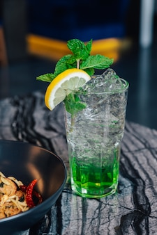 Iced apple soda with sliced lemon and mint leaves in drinking glass on marble top table.