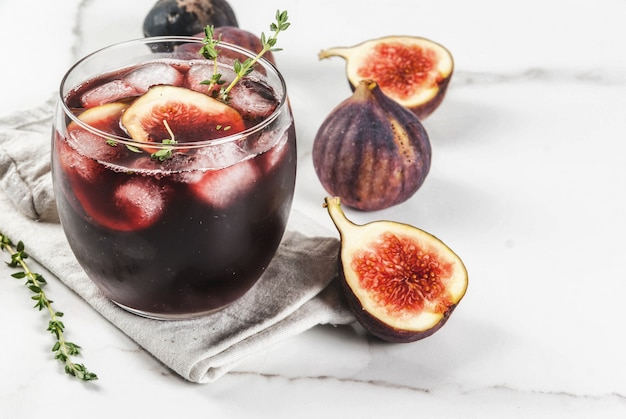 Iced autumn cocktail with red wine, thyme and figs, on white marble table,