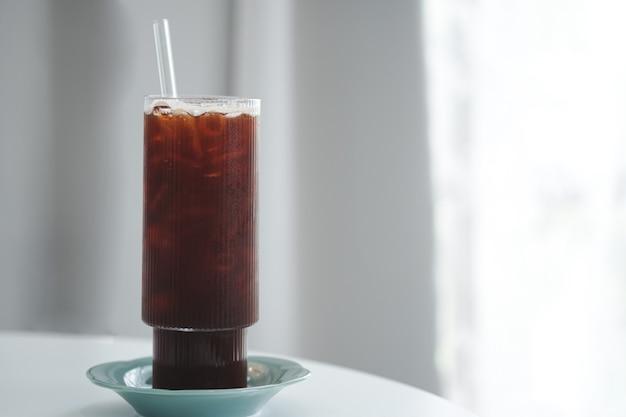 Холодный черный кофе или американо в высоких стаканах с трубочкой и подставками на столике у окна в минималистском кафе. скопируйте пространство.