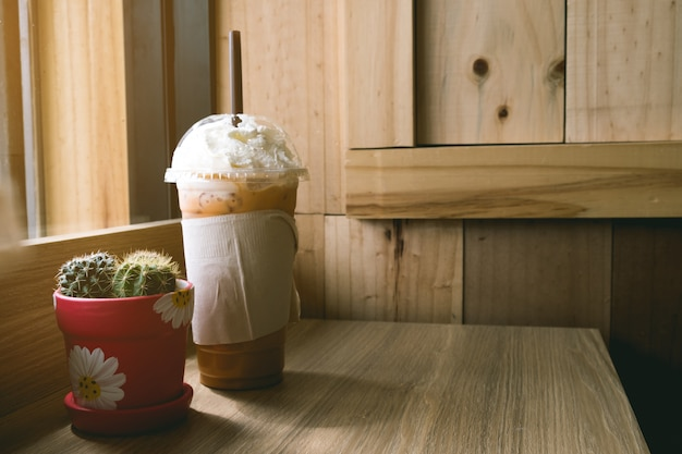 Iced cappuccino with topping cream on wooden table of brown, background