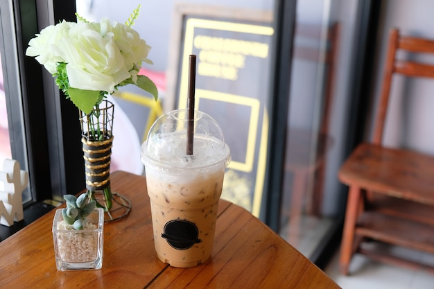 Iced cappuccino on wooden table, white rose