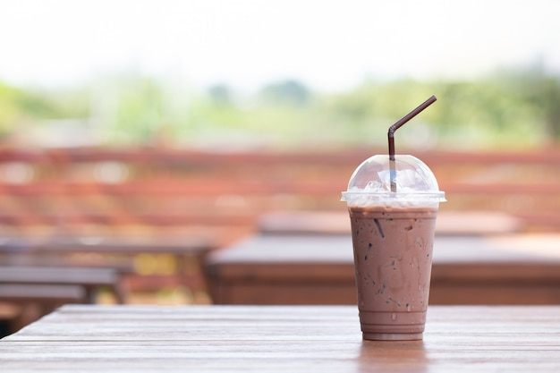 Iced chocolate milkshake, summer refreshment drinks on wooden background in cafe