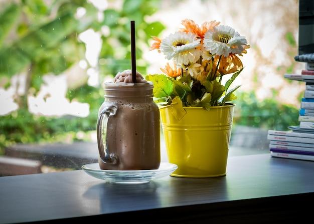 木製のテーブルに人工の花とチョコレートスムージーをアイシング