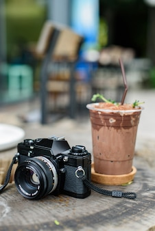 Iced cocoa with film camera on the wooden table