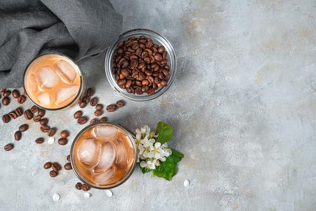 Замороженный кофе и кофейные зерна на серой стене. вид сверху, копия пространства.