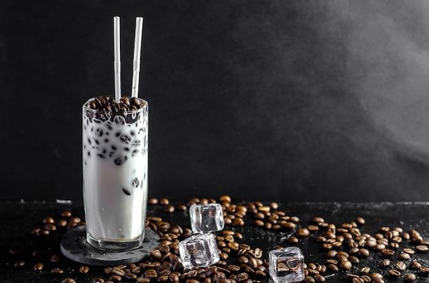 ストローで背の高いグラスにアイスコーヒーフラッペとミルクのコンセプト。暗闇の中でコーヒー豆