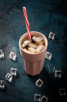 Iced coffee in a glass on a dark blue stone surface with ice cubes. concept cooling drink, thirst, summer, cola with ice, nightlife, club. flat lay, top view