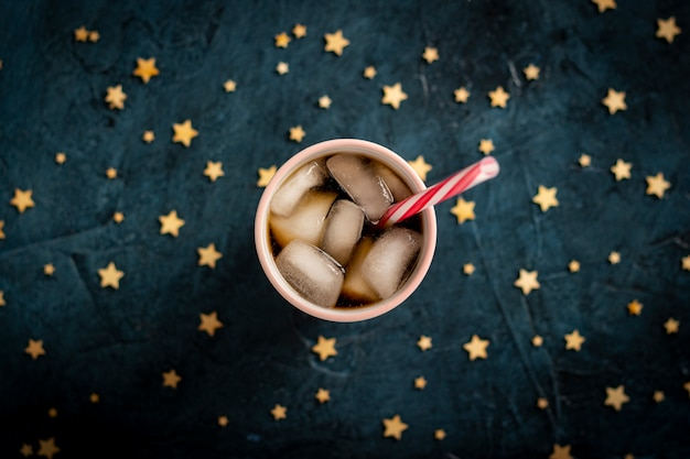 Iced coffee in a glass on a dark blue stone surface with stars.  flat lay, top view