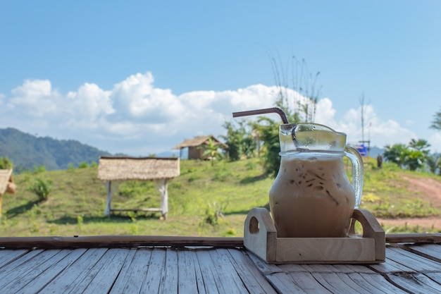 Iced coffee in a glass jar and view wooden house on the mountain.