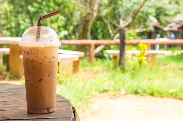 Iced coffee in glass on the table background grass and tree.