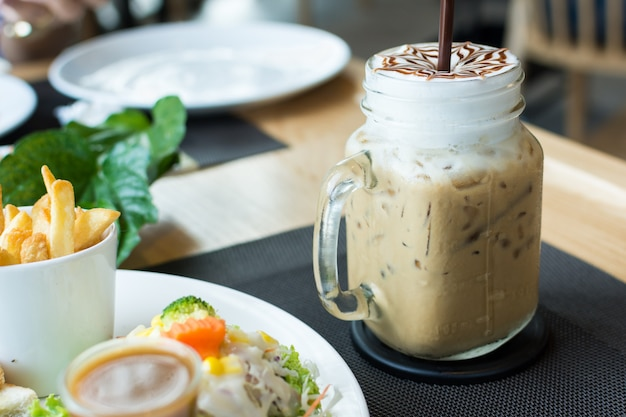 Iced coffee in glass with foods on wooden table