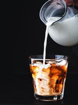 Caffè ghiacciato in un bicchiere con ghiaccio e sciroppo di zucchero