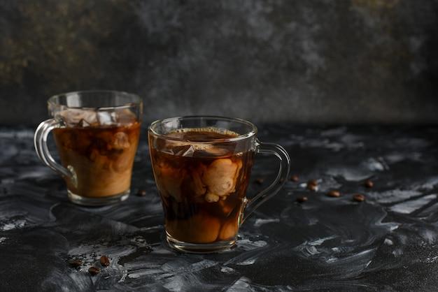 Кофе со льдом в стеклянных чашках со сливками и кофейными зернами