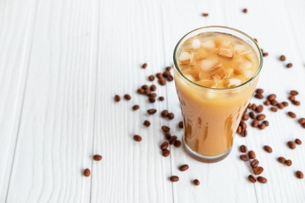 Замороженный кофе в стакане на белом деревянном столе