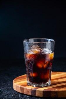 暗い背景上のガラスのアイスコーヒー
