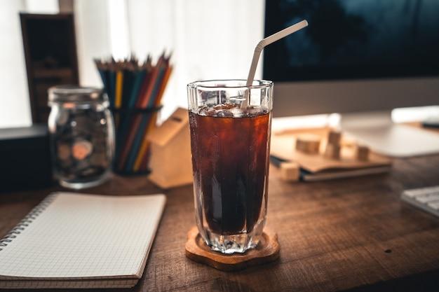 机の上のマグカップにアイスコーヒー、飲み物