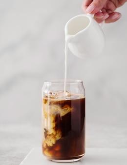 높은 유리잔에 아이스 커피와 크림을 부었습니다. 높은 유리 붓는 크림에 얼음 조각을 넣은 차가운 블랙 커피.