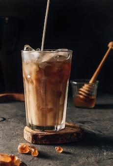 Холодный кофе в высоком стакане со сливками, налитый на темный фон настроения, выборочный фокус