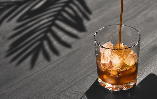 コピースペースのある黒い木製の背景にガラスのアイスコーヒー、コーヒーポットからのコーヒーは氷とガラスに注がれています。冷たいさわやかな夏のコーヒードリンク、明るい日光、ヤシの影の葉
