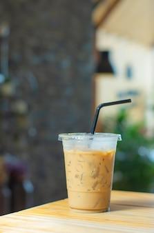 木製のテーブルの上のガラスのアイスコーヒー背景がぼやけています。
