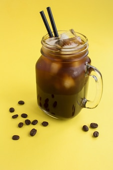 ストローとコーヒー豆とガラスのアイスコーヒー