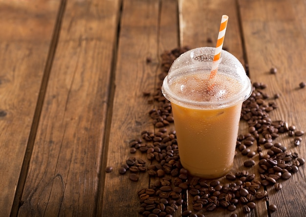 나무 테이블에 콩 플라스틱 유리에 아이스 커피