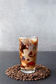 Холодный кофе в высоком стакане со сливками и кофейными зернами вокруг стакана