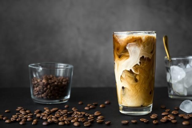 아이스 커피 원두와 크림 용기가있는 키가 큰 유리에 아이스 커피 프리미엄 사진