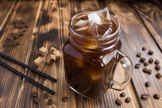 Холодный кофе в стакане на коричневом деревянном столе