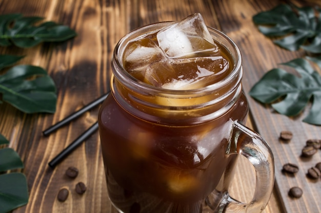 熱帯の背景のガラスのアイスコーヒー。クローズアップ。