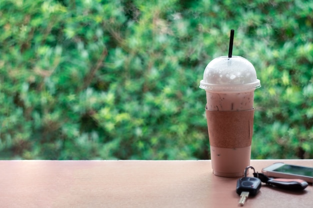 テーブルの上のアイスコーヒー、鍵、スマートフォン。