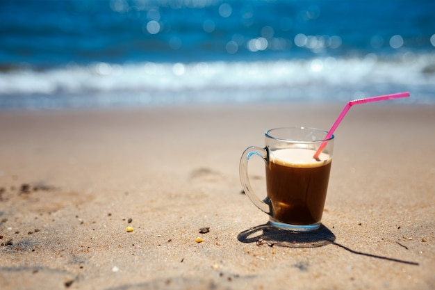 Iced coffee latte on a beach ocean and seascape