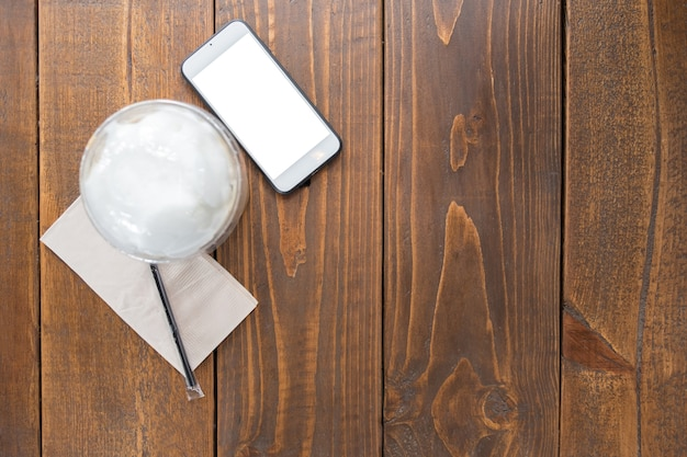 Iced coffee and mobile phone on wooden table of brown