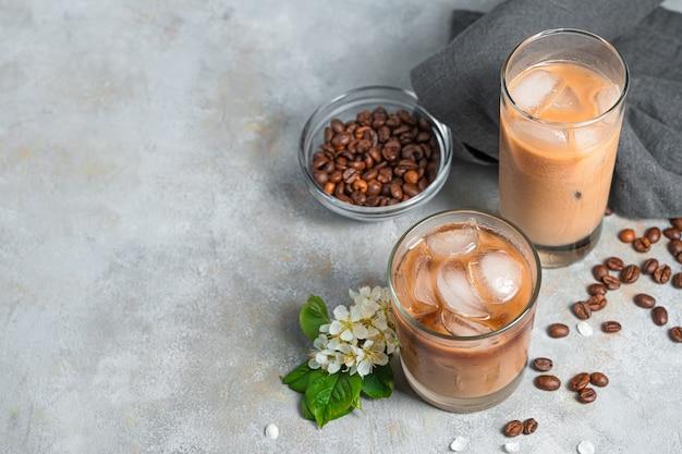 Холодный кофе на серой стене с местом для копирования. два стакана с освежающим молочно-кофейным напитком.