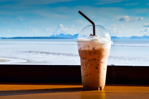 Iced coffee in a plastic cup against the sea